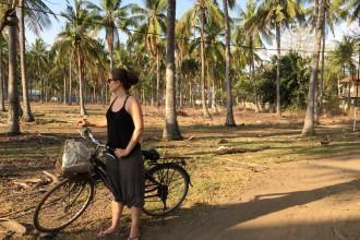 Frau auf Fahrrad unter Palmen