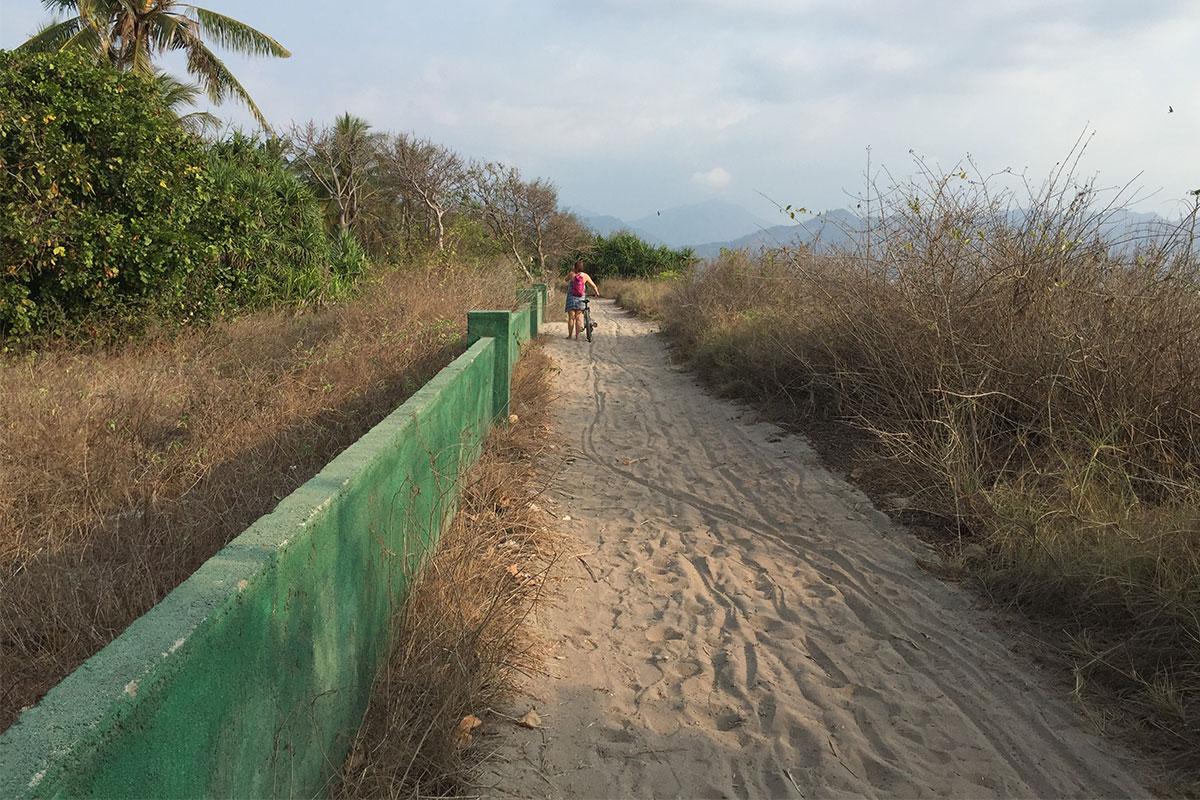 frau-fahrrad-sand-strasse-gili-air