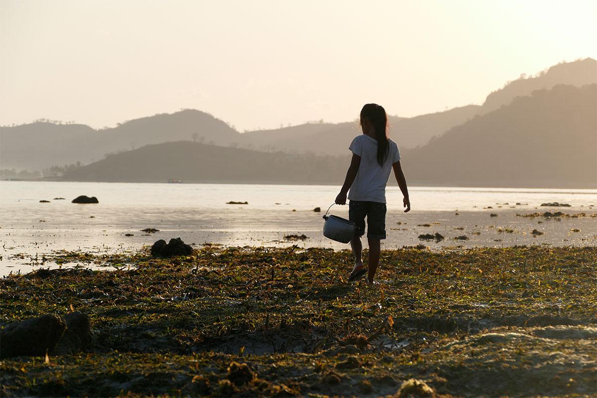 maedchen-mit-eimer-strand-gili-gede-lombok